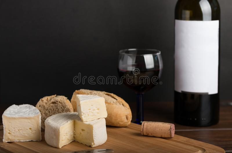 Cheese on wooden table with red wine. Cheese on table with wine and bread stock image