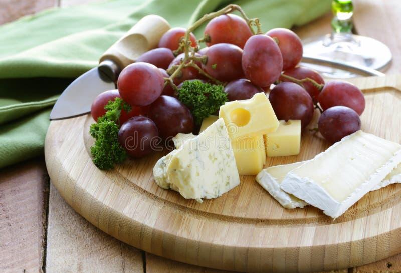 Cheeseboard με το τυρί και τα σταφύλια στοκ εικόνα με δικαίωμα ελεύθερης χρήσης