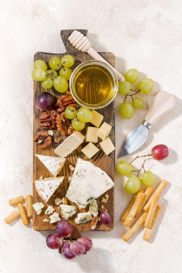 Cheeseboard, φρούτα και μέλι σε ένα άσπρο υπόβαθρο, κάθετο στοκ εικόνες