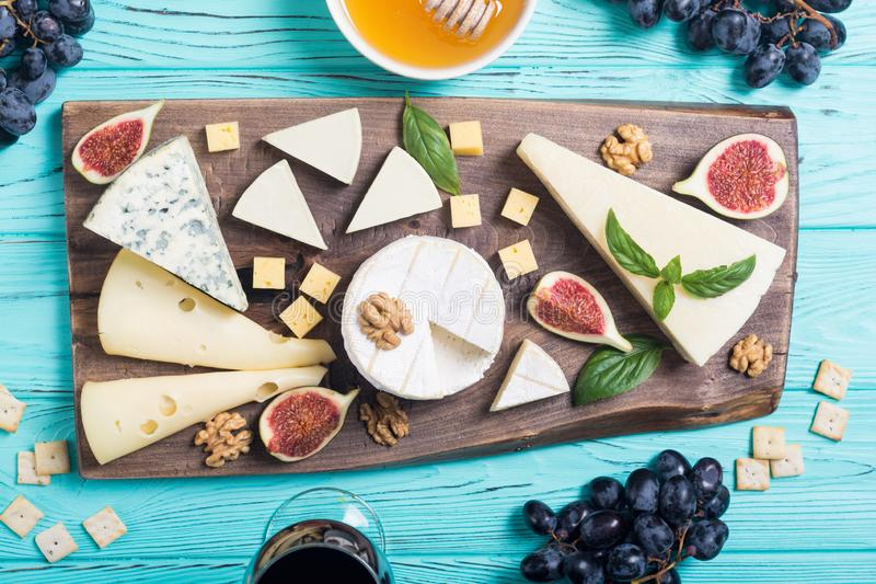 Cheeseboard με brie τυριών την παρμεζάνα, camembert και το dorblu Τρόφιμα στον ξύλινο πίνακα στοκ φωτογραφίες