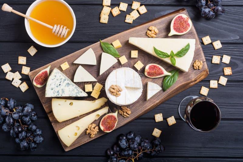 Cheeseboard με brie τυριών την παρμεζάνα, camembert και το dorblu Τρόφιμα στον ξύλινο πίνακα στοκ εικόνες με δικαίωμα ελεύθερης χρήσης