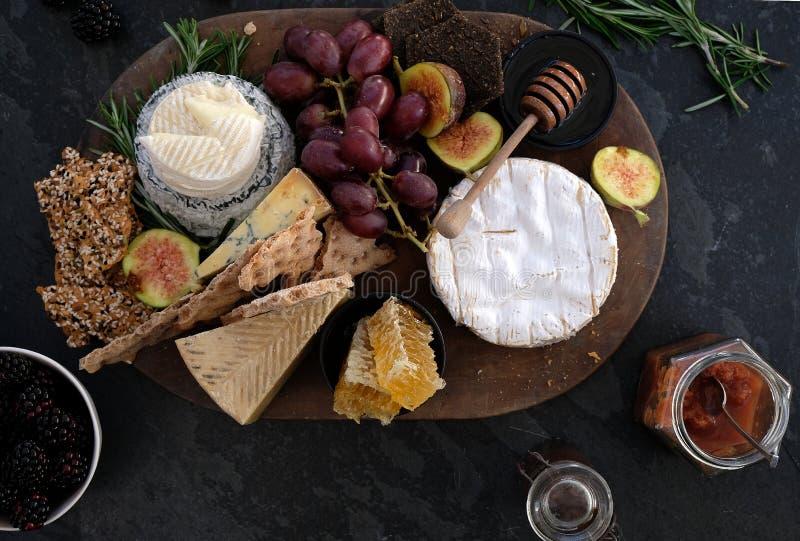 Cheeseboard med en variation av ostar, smällare, frukt, honung, rosmarinkvistar och chutney arkivfoton