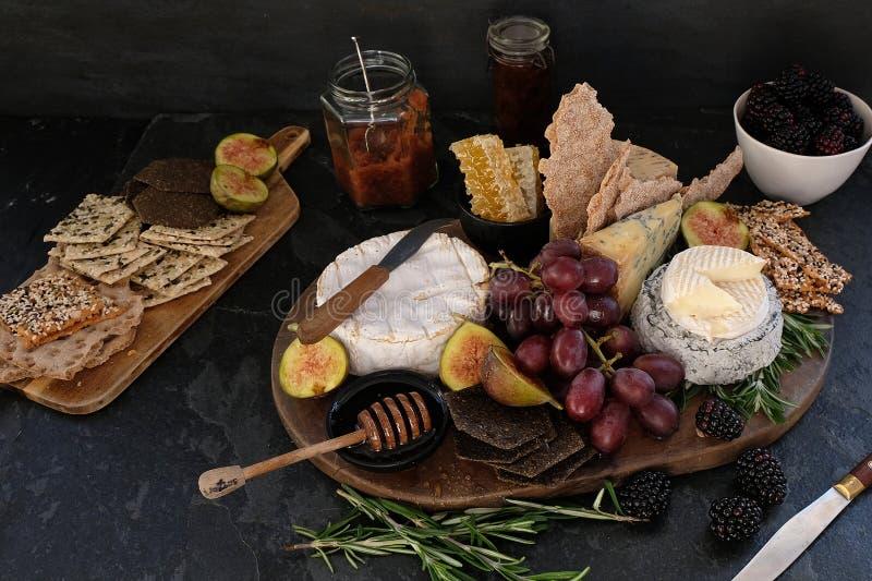 Cheeseboard met een verscheidenheid van kazen, crackers, fruit, honing, rozemarijntwijgen en chutney stock foto's