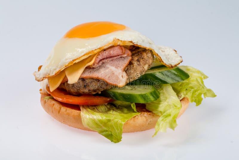 Cheeseburger με cutlet βόειου κρέατος, το μπέϊκον, τις ντομάτες και τις φέτες τυριών, καρύκεψε με τη σάλτσα και την πράσινη σαλάτ στοκ φωτογραφίες