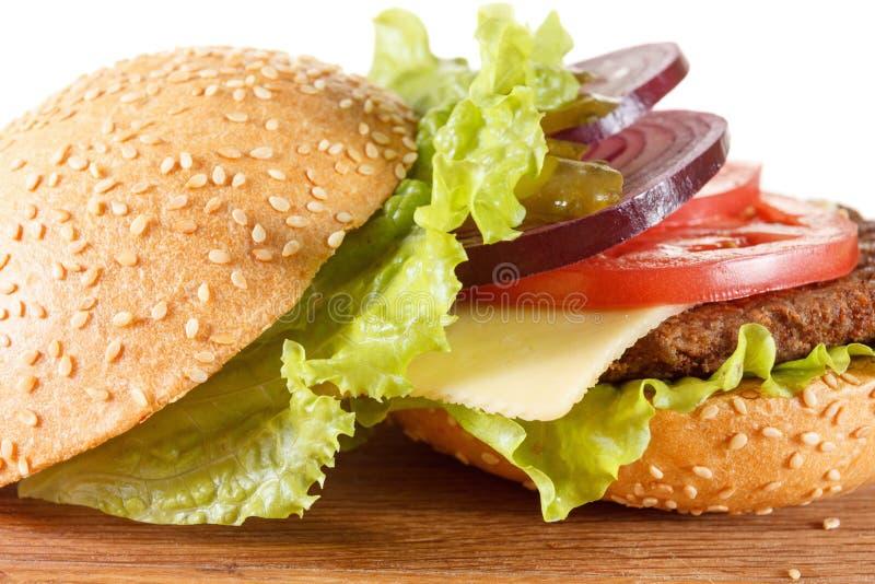 Cheeseburger américain traditionnel La viande, le petit pain et les légumes se ferment  images stock
