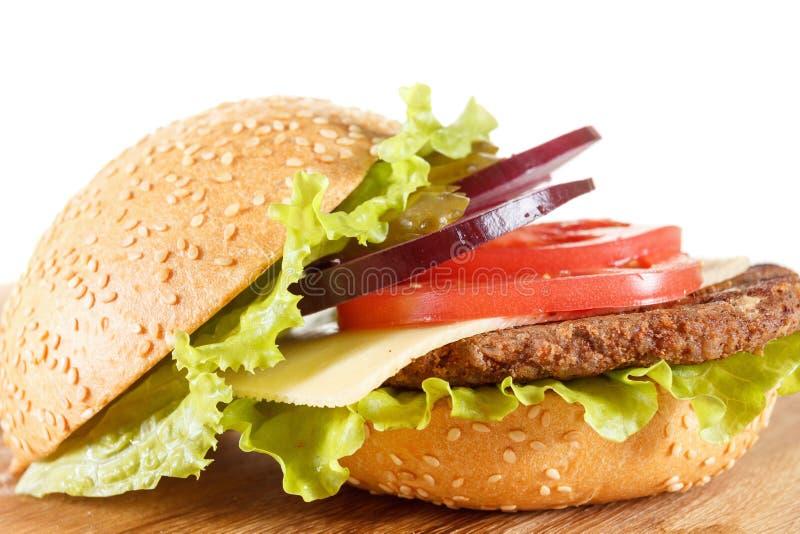 Cheeseburger américain traditionnel La viande, le petit pain et les légumes se ferment  photos libres de droits