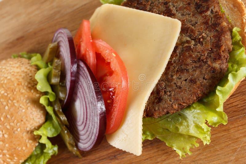 Cheeseburger américain traditionnel La viande, le petit pain et les légumes se ferment  image libre de droits