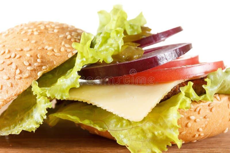 Cheeseburger américain traditionnel La viande, le petit pain et les légumes se ferment  photographie stock