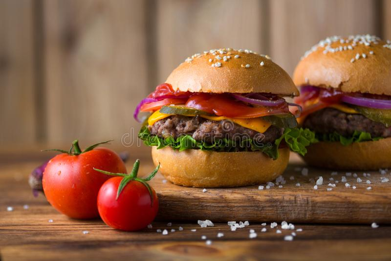 Cheeseburger americano clásico en un tablero de madera con los tomates y la cebolla imagenes de archivo
