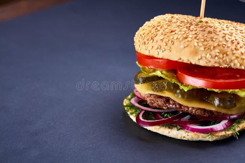 Cheeseburger americano clássico com a bandeira negra na parte superior sobre o fundo escuro, close-up, foco seletivo imagens de stock