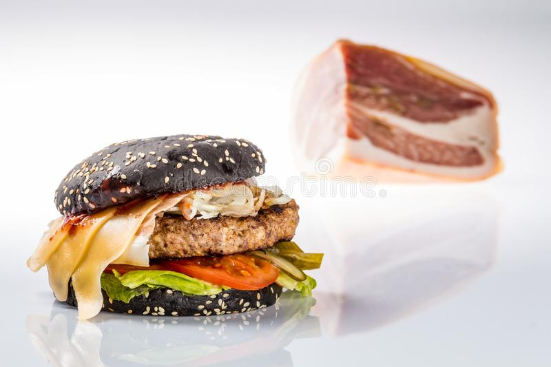Cheeseburger with black bread, beef cutlet, bacon, tomatoes and cheese slices, seasoned with sauce. And green salad for a restaurant menu on a white isolated stock photos