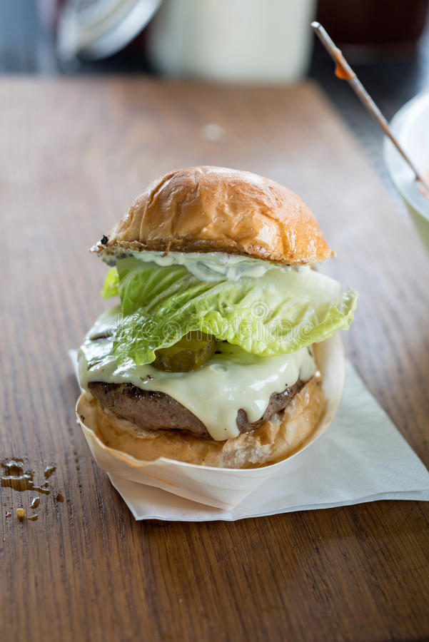 Cheeseburger on a bread bun in a metallic tray. Cheeseburger with lettuce and gherkins in a bread bun in a reflective food tray on a napkin on a wooden surface stock photography