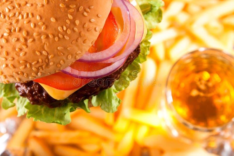 Cheeseburger clássico da carne com fritadas e cerveja imagem de stock