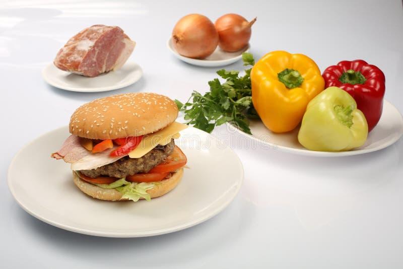 Cheeseburger com o rissol do bacon e de carne em uma placa com vegetais, pimenta de sino, tomates, cebolas, pepino, salsa e salad fotos de stock