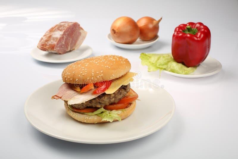 Cheeseburger com o rissol do bacon e de carne em uma placa com vegetais, pimenta de sino, tomates, cebolas, pepino, salsa e salad imagens de stock