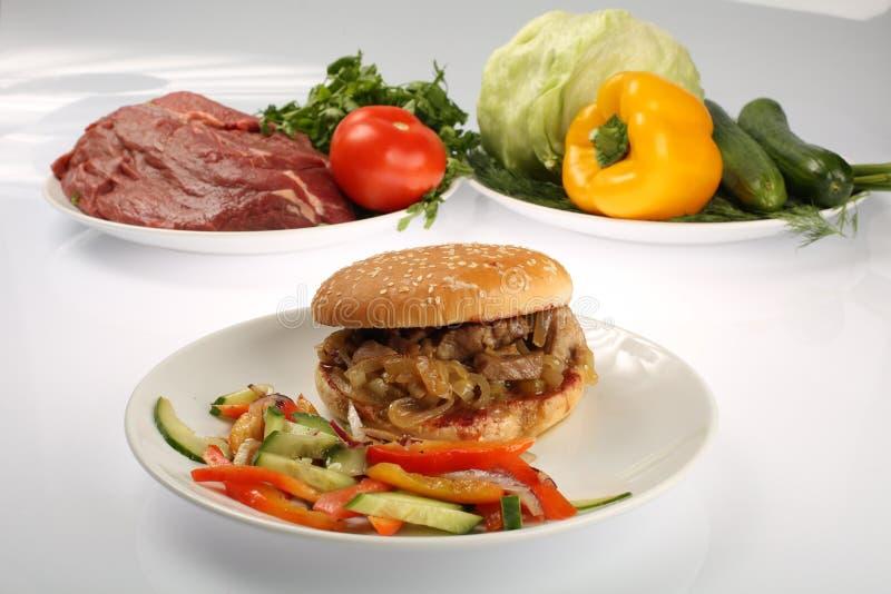 Cheeseburger con il tortino di manzo e del bacon su un piatto con le verdure, il peperone dolce, i pomodori, le cipolle, il cetri immagini stock libere da diritti