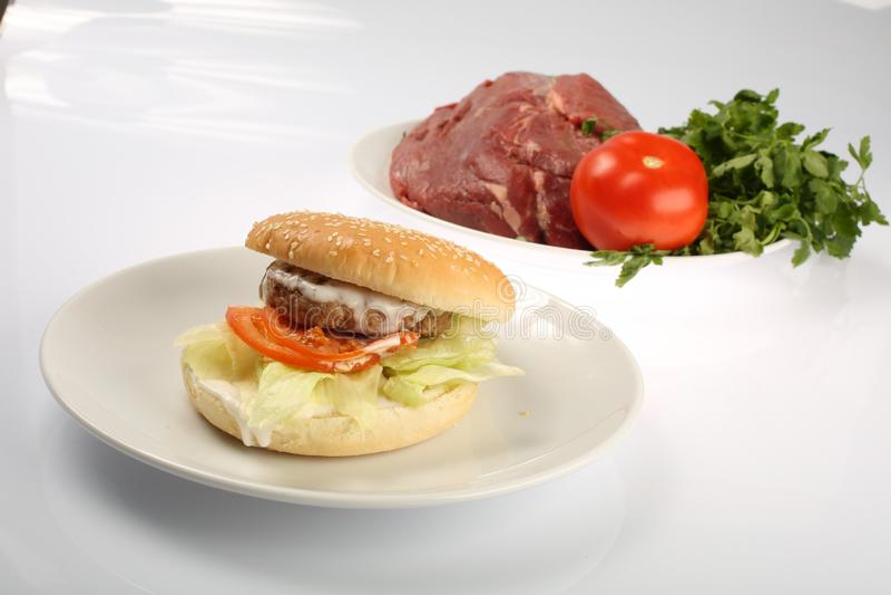 Cheeseburger con il tortino di manzo e del bacon su un piatto con le verdure, il peperone dolce, i pomodori, le cipolle, il cetri fotografie stock libere da diritti