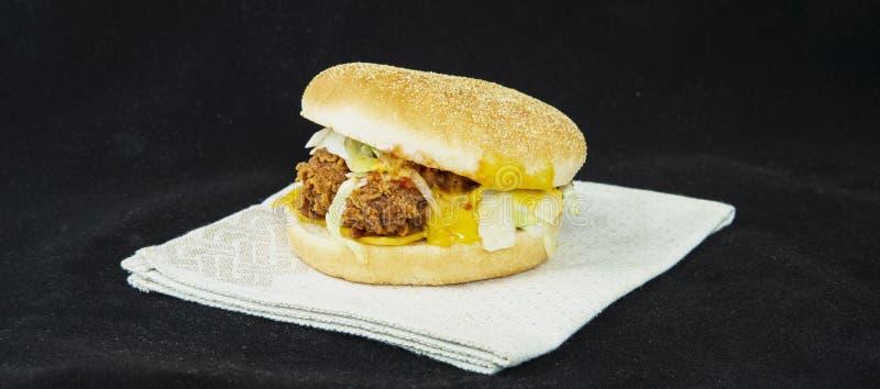 Cheeseburger con insalata di verdure e carne al forno in un panino per il giorno di hot dog nazionale immagine stock libera da diritti