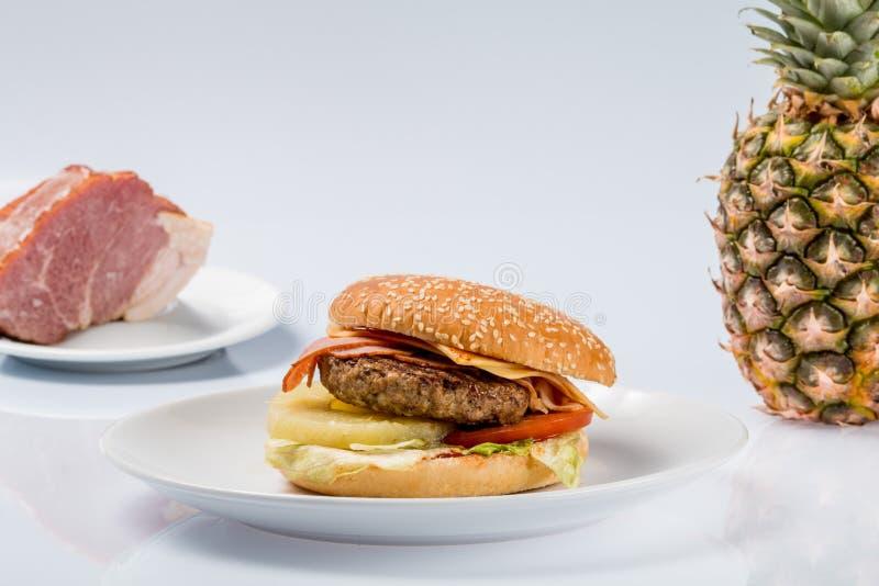 Cheeseburger con l'ananas su un piatto con bacon fresco e l'ananas maturo immagini stock