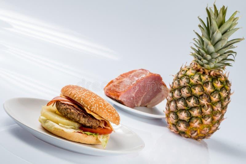Cheeseburger con l'ananas su un piatto con bacon fresco e l'ananas maturo fotografia stock libera da diritti