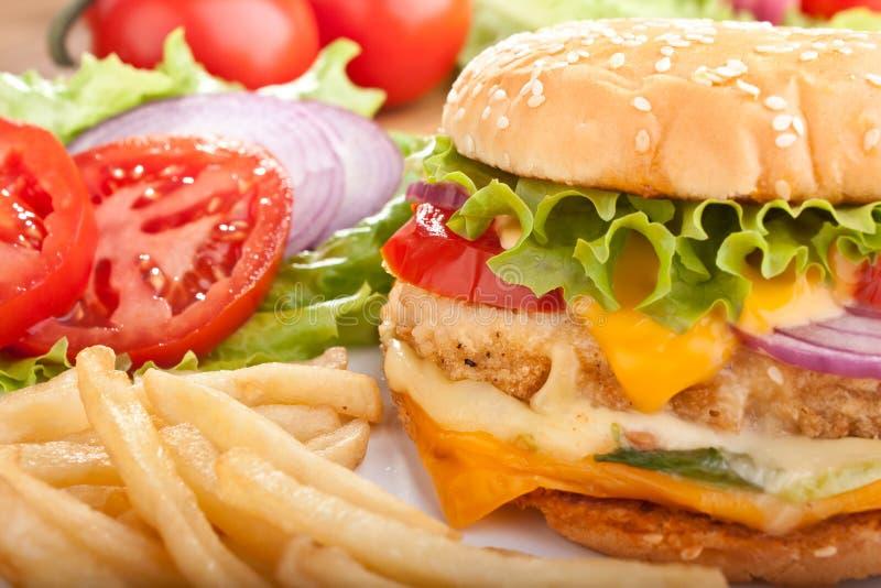 Cheeseburger con le fritture e gli ingredienti fotografie stock libere da diritti