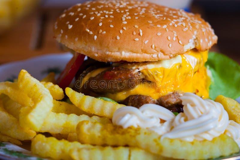 Cheeseburger con le patate fritte immagine stock