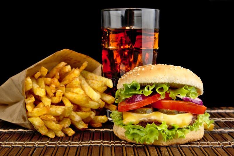 Cheeseburger con le patate fritte con vetro di cola sulla stuoia di legno sul nero fotografia stock