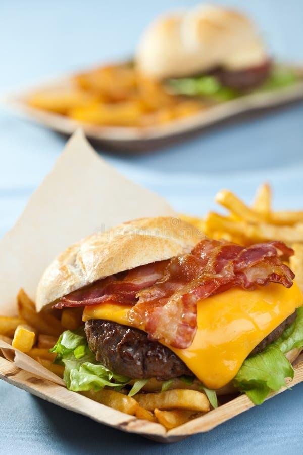 Cheeseburger con tocino y fritadas imagenes de archivo
