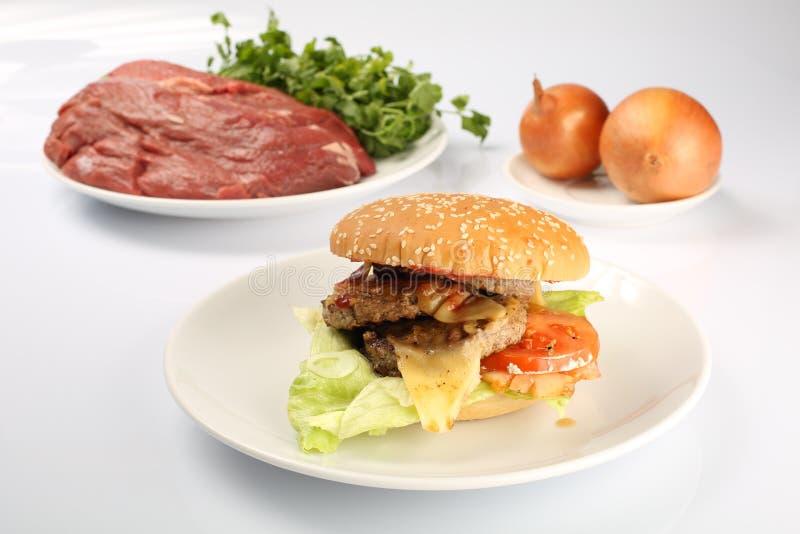 Cheeseburger, cotoletta del pollo, bacon, pomodori e fette di formaggio, vestiti con salsa ed insalata verde per un menu del rist immagine stock libera da diritti