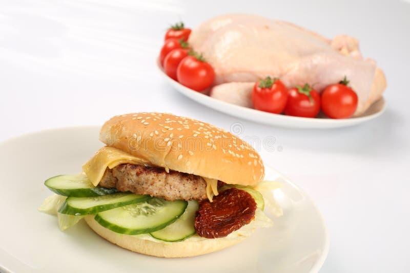 Cheeseburger, cotoletta del pollo, bacon, pomodori e fette di formaggio, vestiti con salsa ed insalata verde per un menu del rist fotografia stock