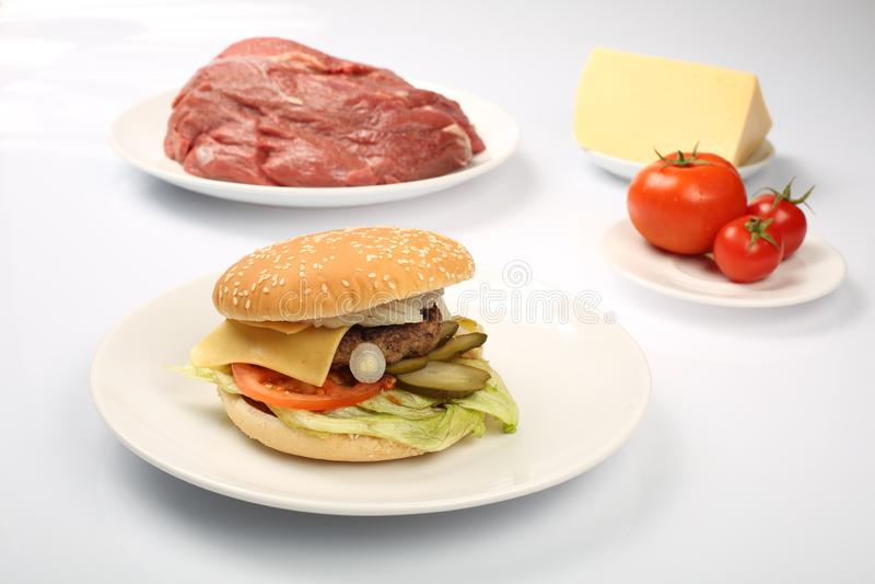 Cheeseburger, cotoletta del pollo, bacon, pomodori e fette di formaggio, vestiti con salsa ed insalata verde per un menu del rist fotografie stock libere da diritti