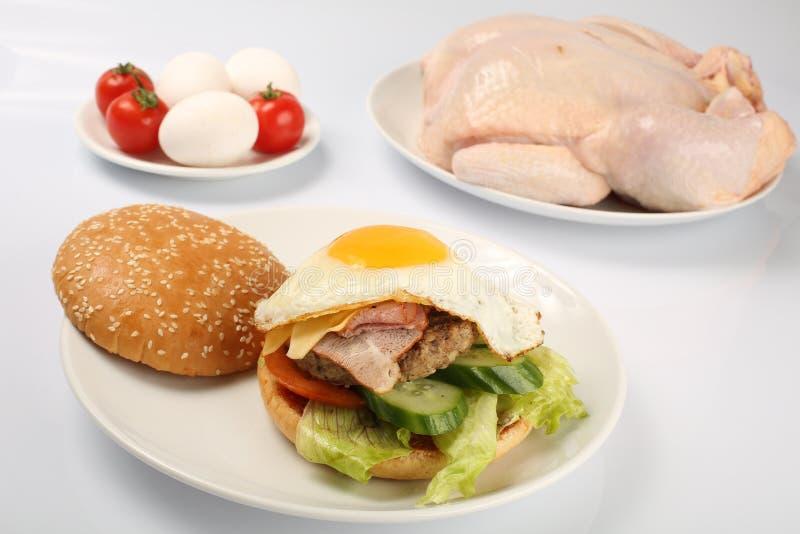 Cheeseburger, cotoletta del pollo, bacon, pomodori e fette di formaggio, vestiti con salsa ed insalata verde per un menu del rist immagine stock