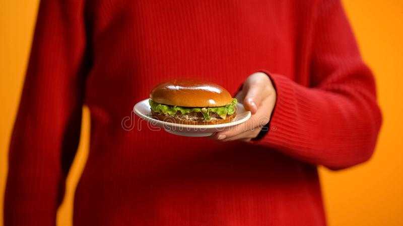 Cheeseburger d'apparence de femme de plat, ob?sit? d'aliments de pr?paration rapide, soins de sant?, calories photo stock