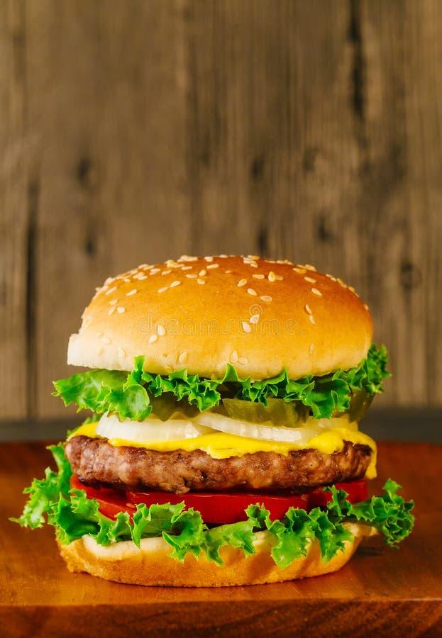 Cheeseburger de luxe classique avec de la laitue, les oignons, la tomate et les conserves au vinaigre photographie stock