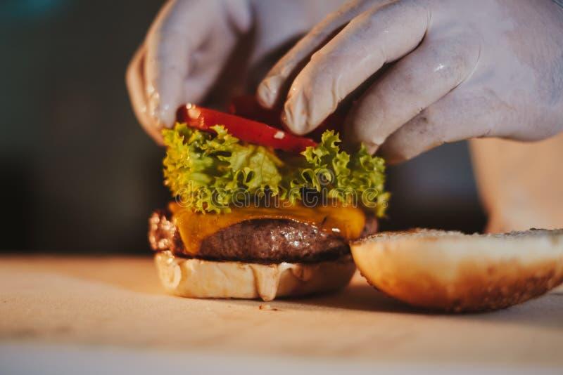 Cheeseburger de montagem do cozinheiro chefe da cozinha adicionando o tomate foto de stock royalty free