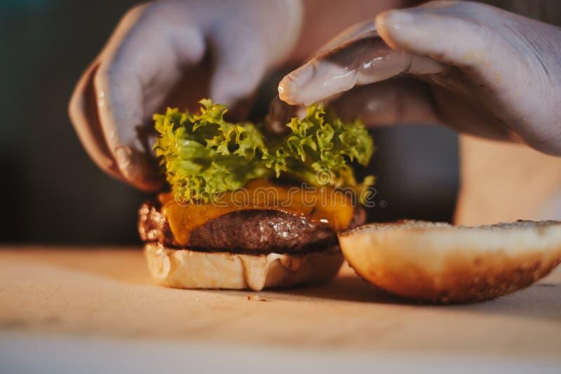 Cheeseburger de montagem do cozinheiro chefe da cozinha adicionando a salada foto de stock