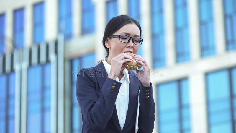 Cheeseburger de mordedura do gerente fêmea com fome, petisco do fast food, nutrição insalubre fotografia de stock royalty free