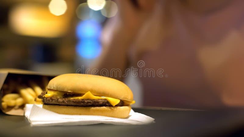 Cheeseburger e batatas fritas deliciosos na tabela, jantar do fast food, perda de peso imagem de stock