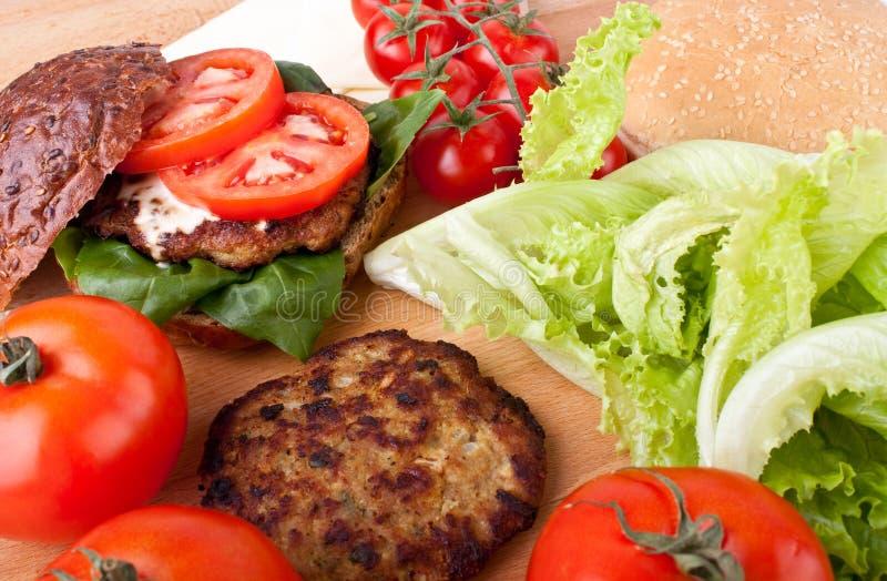 Cheeseburger e ingredientes fotografia de stock royalty free