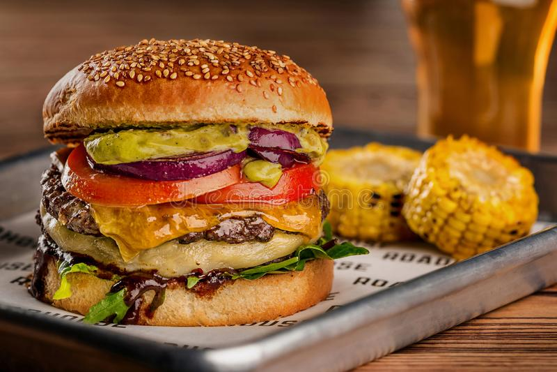 Cheeseburger, fait à partir du petit pain de seigle avec la tranche de tomate et du fromage fondu sur un boeuf rôti, et la feuill image stock