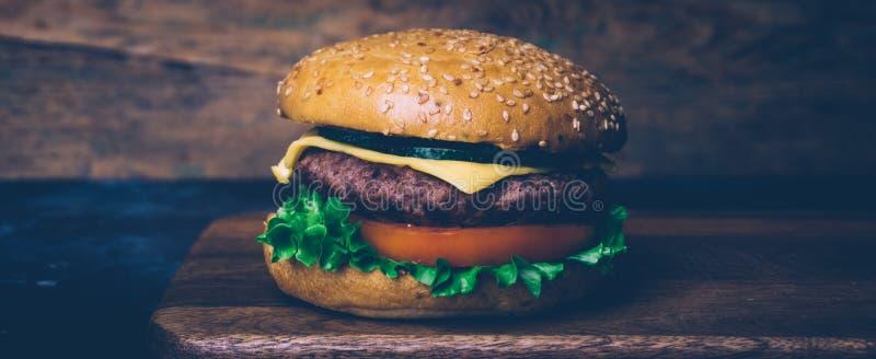 Cheeseburger hecho casero de la hamburguesa con carne de vaca en un fondo de madera La obra clásica a casa hizo la hamburguesa Ci imagen de archivo libre de regalías