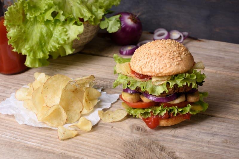 Cheeseburger juteux sur la table en bois avec les pommes chips et le ketchup photographie stock libre de droits