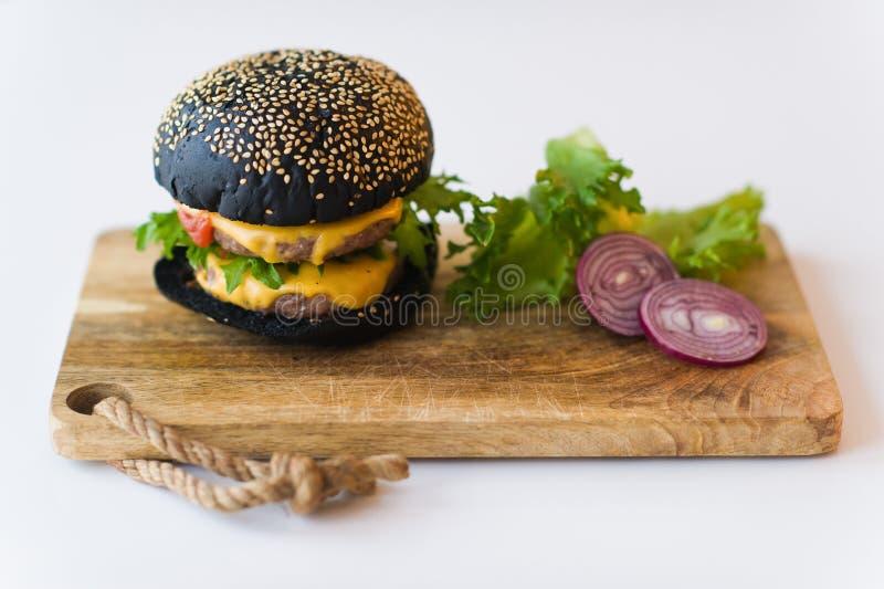Cheeseburger nero sul tagliere di legno, fondo grigio fotografia stock