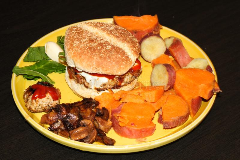 Cheeseburger plate with sweet potatoes stock images