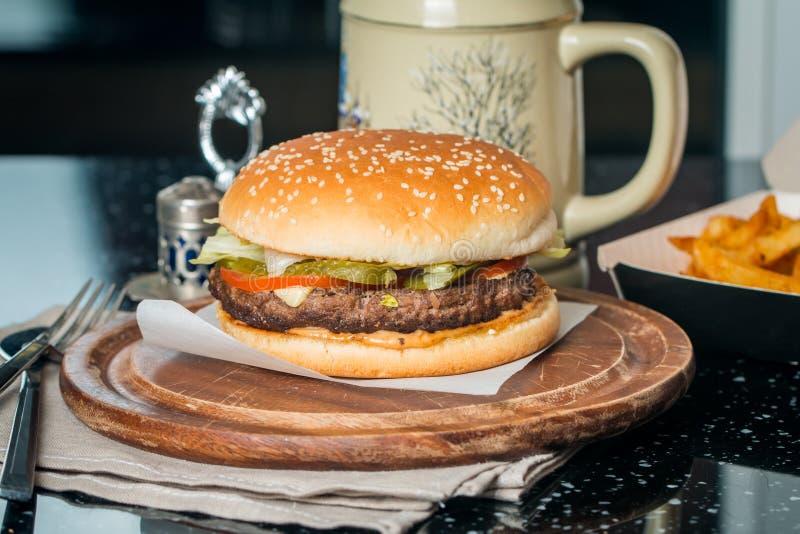 Cheeseburger servido con las patatas fritas y la cerveza imagen de archivo libre de regalías