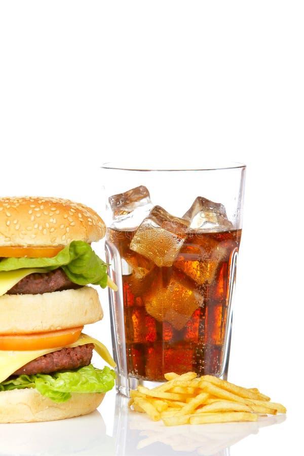 Cheeseburger, soda y patatas fritas dobles imagenes de archivo