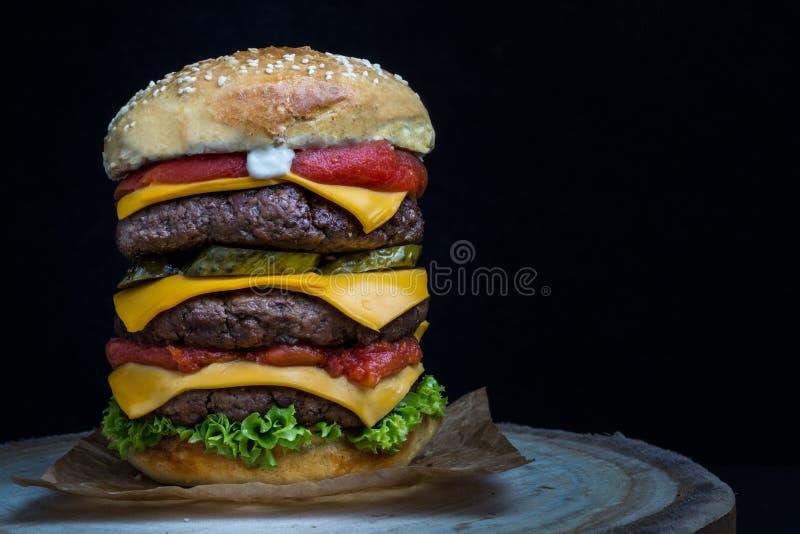 Cheeseburger triplo com tomate, alface, salmouras e maionese imagem de stock royalty free