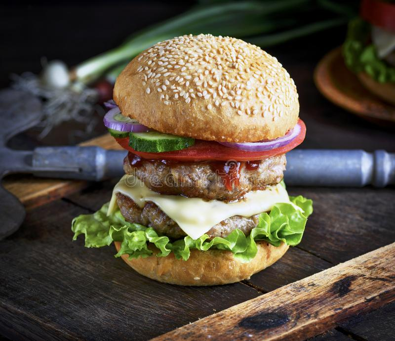 Cheeseburger in un panino con i semi di sesamo, nel veg fresco medio fotografie stock