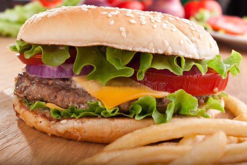 Cheeseburger und Pommes-Frites mit Bestandteilen stockfotografie