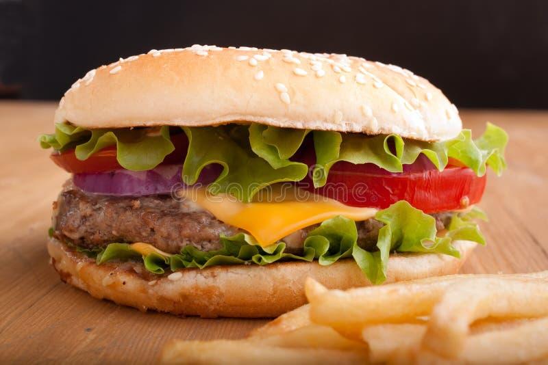 Cheeseburger y patatas fritas en un vector de madera imagenes de archivo
